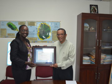 Mrs. Claricia Langley Stevens presenting the certificate to Permanent Secretary Mr. Osmond Petty